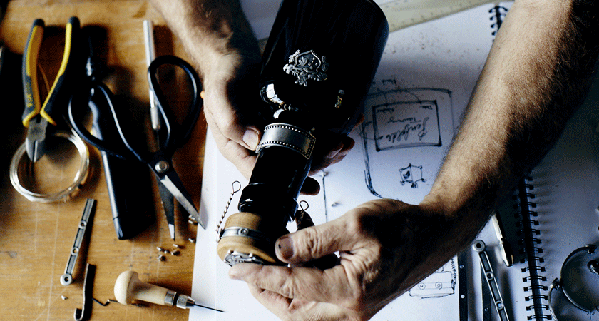 Overhead of 50 year old rare tawny bottle being assembled. Sketches appear under the bottle