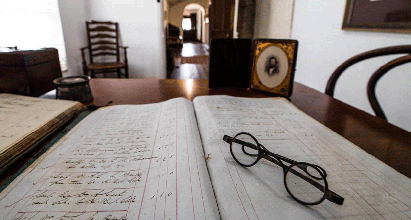 The view from Dr Christopher Penfold's desk in the Grange cottage. Original handwritten logbook appears under reading glasses