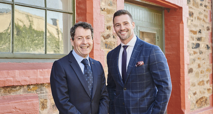 Peter Gago and Kris Smith stand against heritage brick building