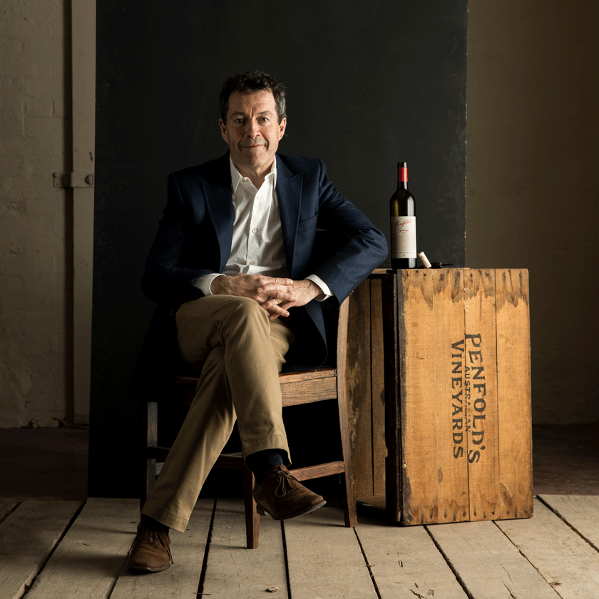 Peter Gago, Penfolds Chief Winemaker, sits inside on a chair facing the camera.  A bottle of Grange sits beside him on a wooden Penfolds crate.