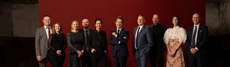 The Penfolds Winemaking Team.  10 people stand with red background behind.