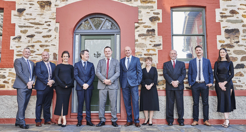 Penfolds winemaking team stand against heritage brick building