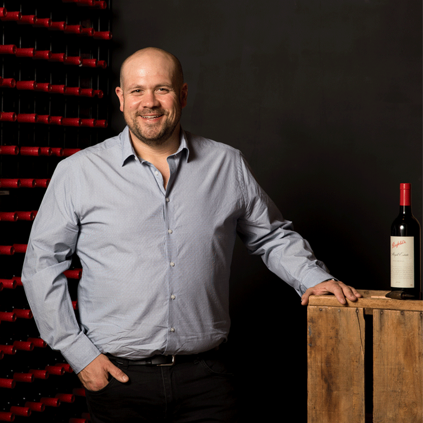 Matt Woo, Penfolds Winemaker, stands with a bottle of wine beside him and rows of red Penfolds bottles behind