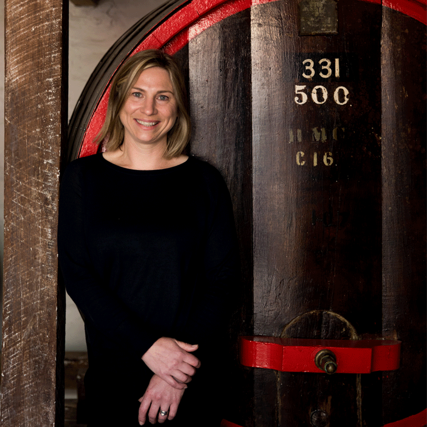 Emma Wood, Penfolds Winemaker, stands in front of a large wine aged wine vat