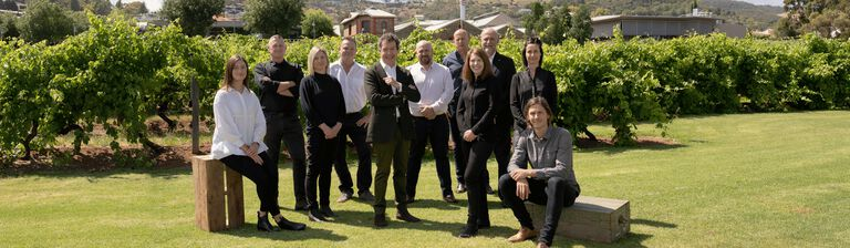 The Penfolds Winemaking Team on the lawns of Magill Estate.  11 people stand with vineyard and heritage brick buildings visible behind.