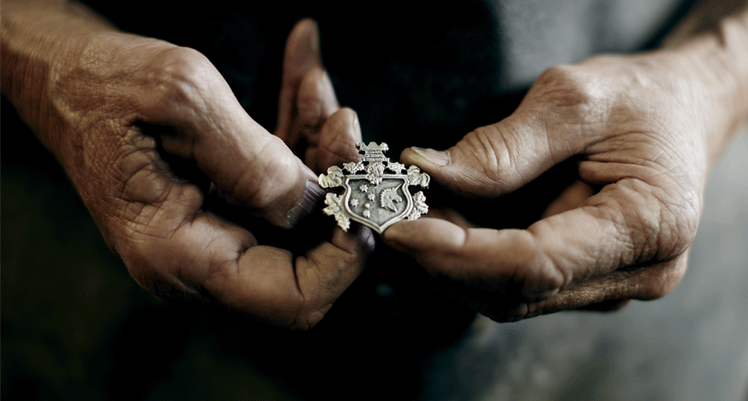 Handcrafted metal crest being held by two weathered hands