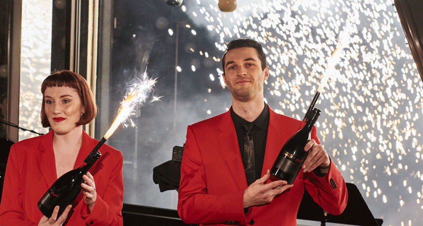 Sparklers being held by waiters in champagne bottles