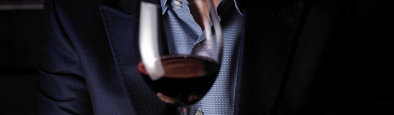 Person in blazer and blue shirt holds red wine glass