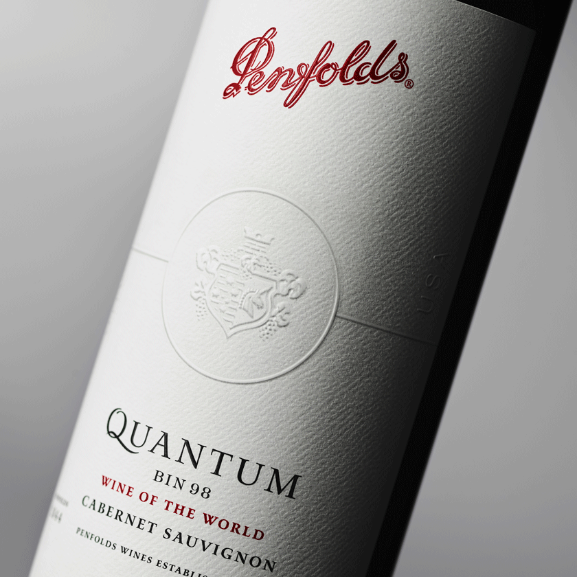Close up of Quantum Bin 98 Cabernet label. Paper is a textured white.  Penfolds logo at the top, embossed crest.  At the bottom of the label it says 'Wine of the World'
