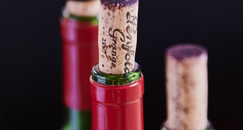 Three Penfolds Grange bottles.  Very close up with the cork removed and sitting in the top of the bottles