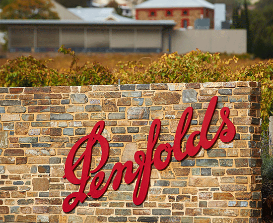 Penfolds red logo on brick fence. Entrance sign to Magill Estate Winery