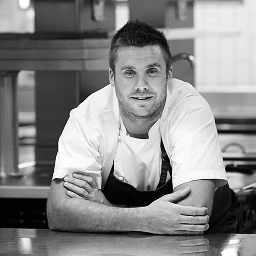 Scott Huggins, Head Chef, leans on kitchen bench