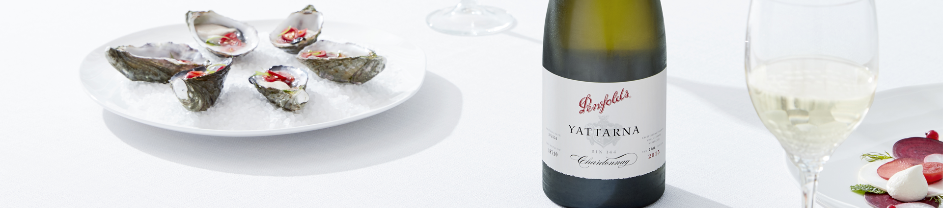 Bottle of Yattarna Chardonnay centred on a white tablecloth.  A glass to the right and a plate of oysters to the left.