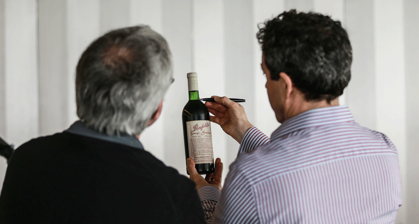 Peter Gago checks ullage level of a Penfolds wine bottle