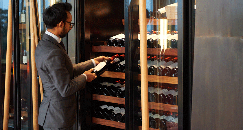Restaurant Sommelier selects a wine from the wine fridge