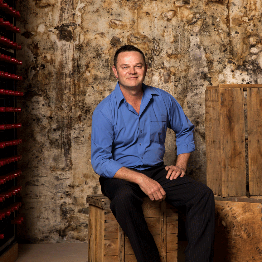 Kym Schroeter, Penfolds White Winemaker, sits on wooden crates.  He is wearing a blue shirt and red Penfolds bottles are visible in the background.