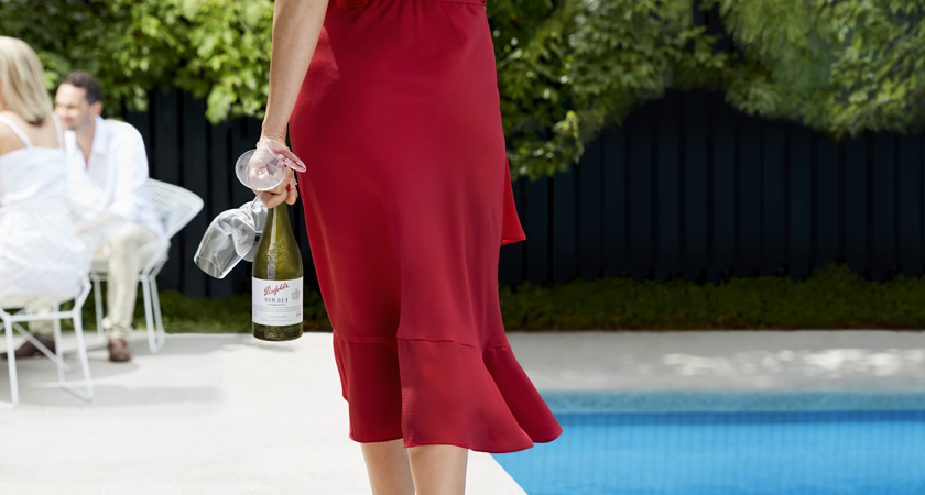 Lady stands in red dress holding bottle of Penfolds Bin 311 Chardonnay