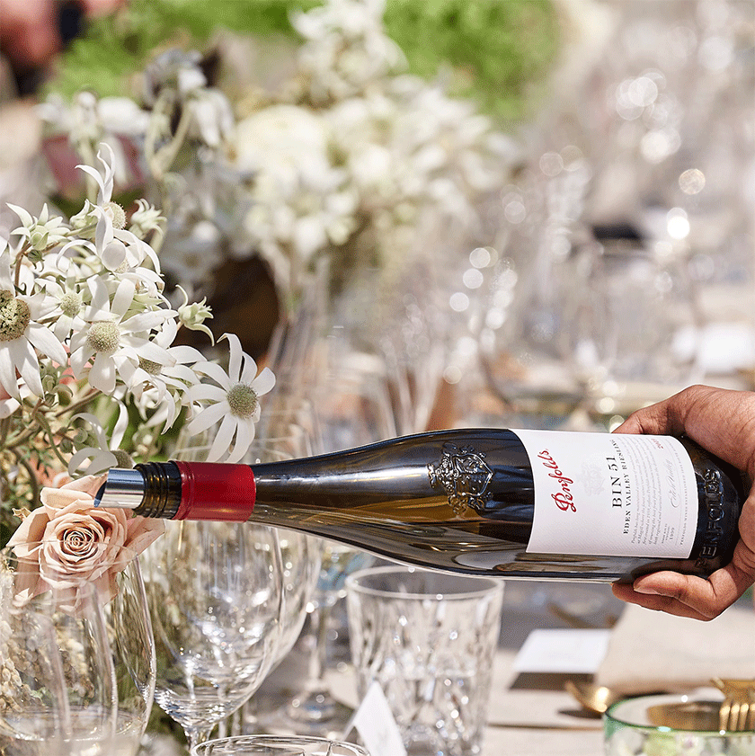Bin 51 Riesling being poured over a set table with white florals behind