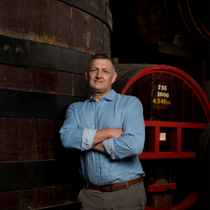 Andrew Baldwin, Penfolds Red Winemaker, stands in front of large wine barrels