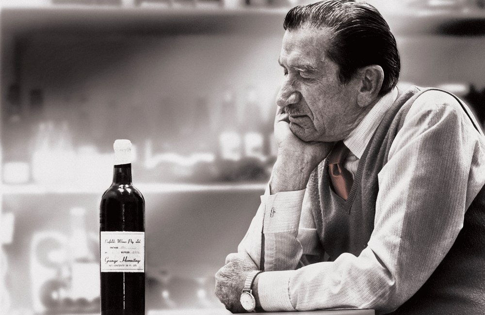An older Max Schubert looks at an early release Grange bottle