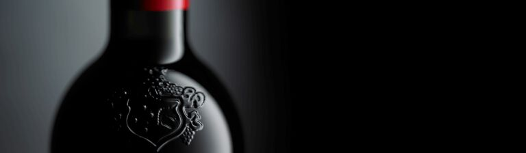 Close up of a neck of a Penfolds bottle. Embossed crest is visible on glass and Penfolds red capsule