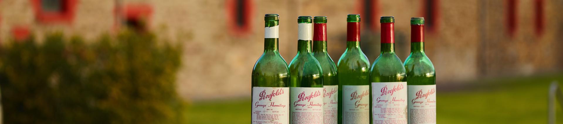 A row of heritage Grange bottles outside. Heritage brick building behind