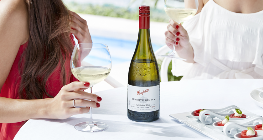 Reserve Bin A Chardonnay bottle on a white table cloth.  Two ladies drink wine over lunch.