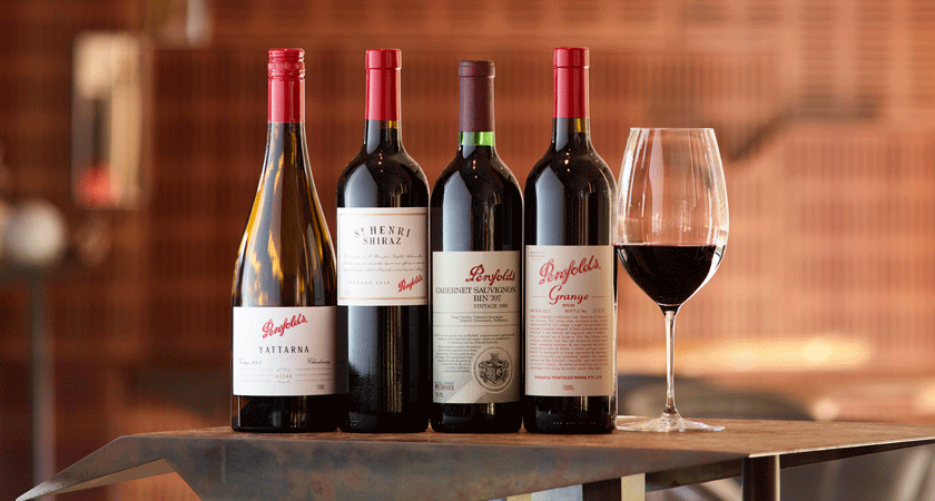Luxury wine pairing.  Four bottles next to a glass of red wine.