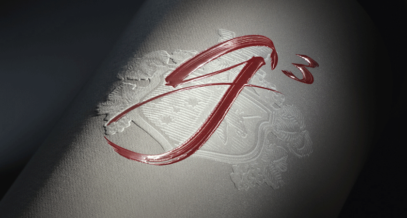 Close up of Penfolds g3 front label.  Red calligraphy script shows g ^ 3.  A embossed crest is visible behind.