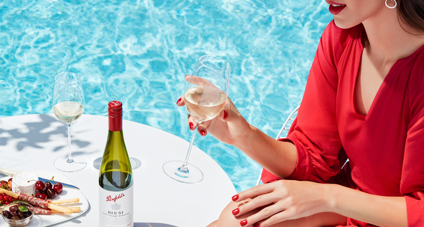 Bottle of Bin 51 Riesling on table with antipasto.  Lady in red dress holds glass beside table. Pool is in the background.