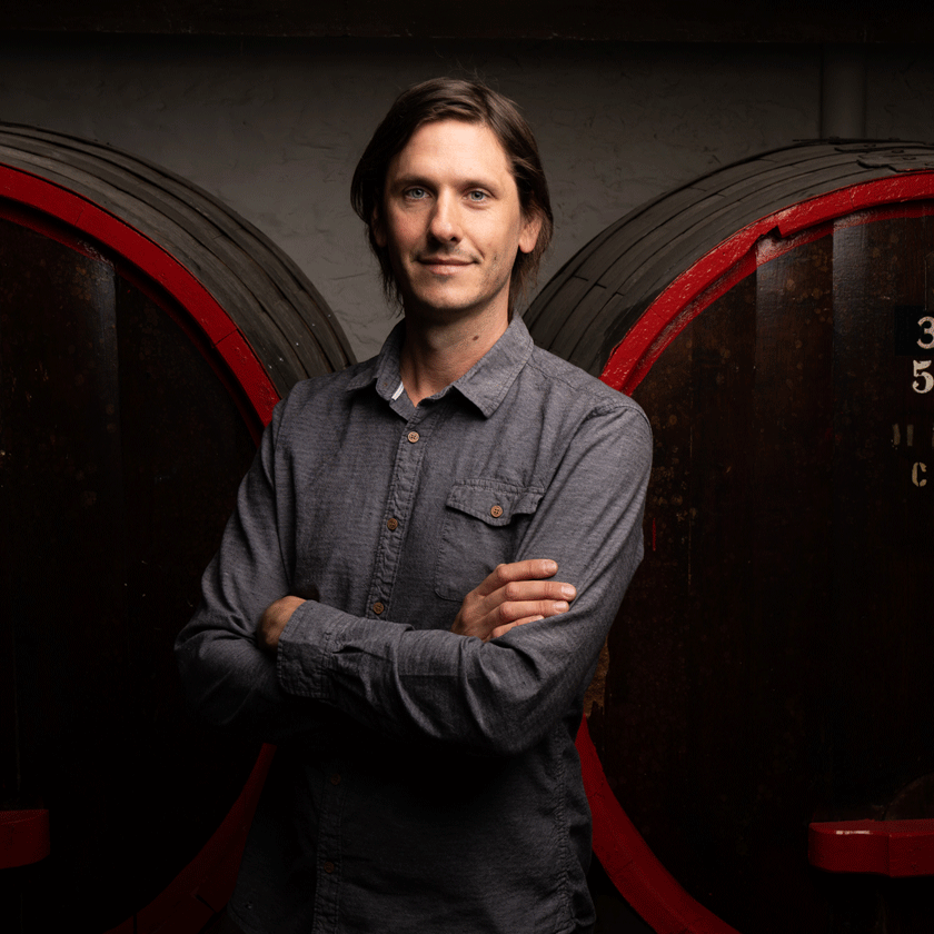 Dominic Coulter, Penfolds Winemaker, stands in front of a large wine aged wine vats