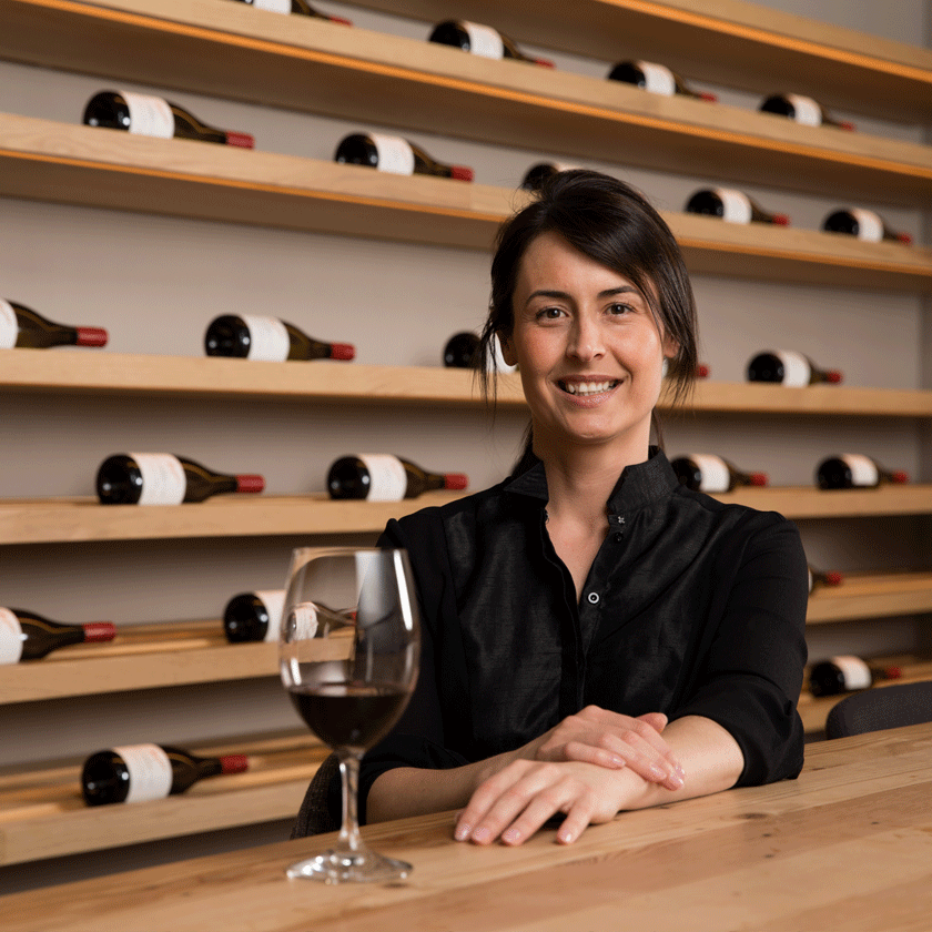 Steph Dutton, Penfolds Senior Winemaker, sits at a light wood table with rows of wine bottles behind her.