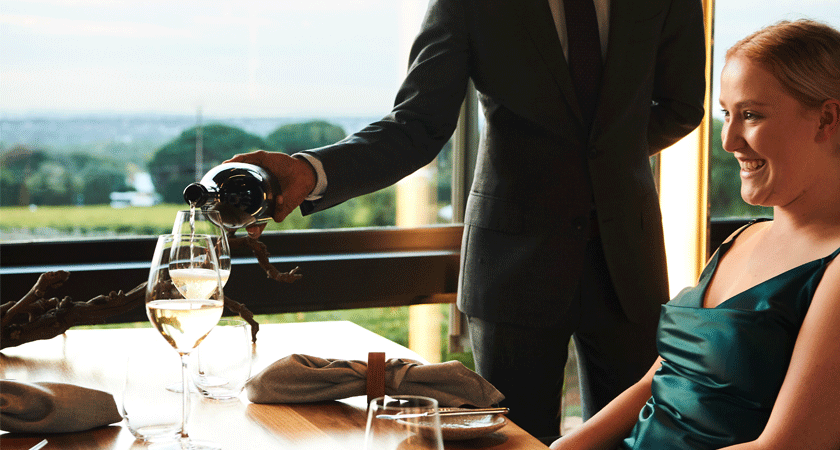 Sommelier pours wine to diner at sunset