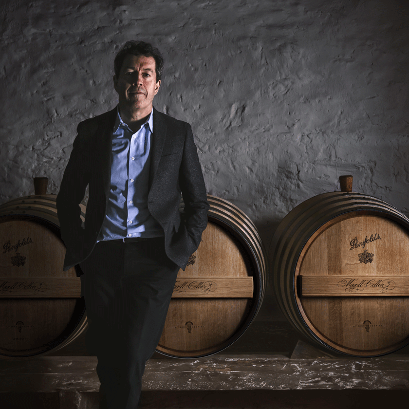 Peter Gago, Penfolds Chief Winemaker, stands in front of Magill Cellar 3 barrels
